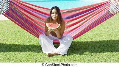Hungry woman biting into watermelon slice