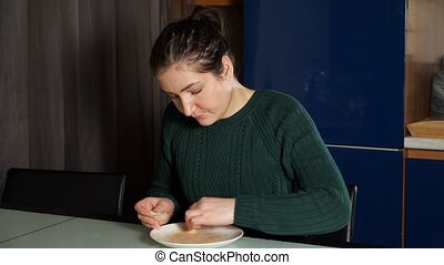 hungry young woman in green knitted sweater sits at table and eats lunch licking leftover food off plate close view