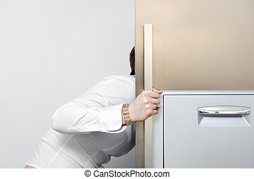 hungry woman looking into fridge. Copy space