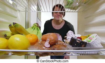 Woman on a low calorie diet choosing food inside fridge.