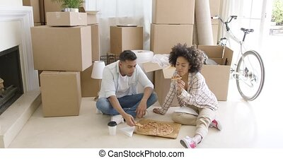 Hungry young couple eating a pizza on the floor