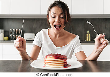 Hungry young woman sitting at the kitchen in home
