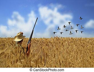 A man hunting ducks in a grain field