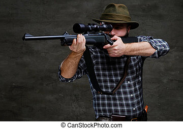 Hunter aiming a rifle in sight while preparing to make an accurate shot at the prey.