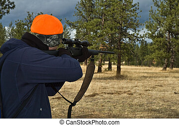 Hunter aiming a rifle into the woods