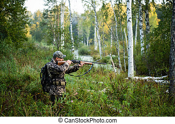 Hunter aiming with weapon at the outdoor hunting