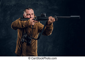 Hunter holding a rifle and aiming at his target or prey. Studio photo against a dark wall background