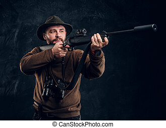 Hunter holding a rifle and aiming at his target or prey. Studio photo against dark wall background
