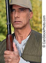 Hunter holding a shotgun close to his face