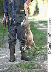 Hunter holding dead rabbit