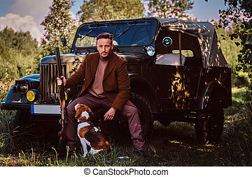 Hunter in elegant clothes holds a shotgun and sits together with his beagle dog while leaning against a retro military car in the forest.