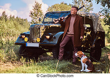 Hunter in elegant clothes holds a shotgun and standing together with his beagle dog near a retro military car in a forest.