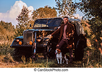 Hunter in elegant clothes standing together with his beagle dog near a retro military car in a forest.