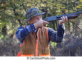 Hunter In Fall - Hunter shooting a shotgun in a field in...