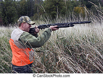 hunter in marsh grass with an orange safety vest