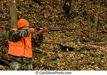 hunter in safety orange aiming shotgun with a fall leaves...