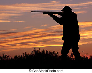a hunter with shotgun silhouetted in the sunset