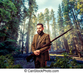 Portrait of breaded hunter man in vintage hunting clothing with old gun, green forest on background. Hunt lifestyle