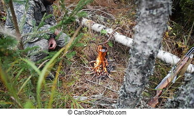 Hunter man at a fire in the forest