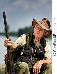Hunter - Senior hunter with shotgun sitting beside lake