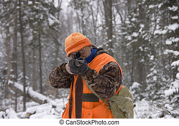 Senior hunter aiming a deer in his sight under the snow, Quebec, Canada