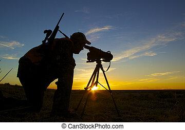 Hunter Spotting at Sunset - a rifle big game hunter looking...