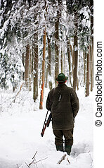 Hunter, armed with a rifel, standing in a snowy forest