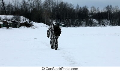 Hunter goes on trail, on the frozen river bed