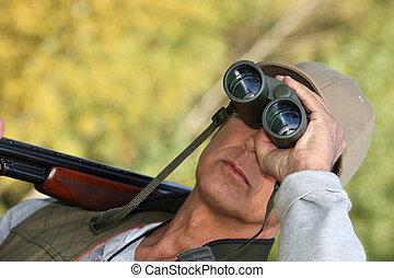 Hunter watching through binoculars