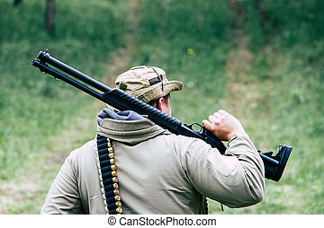 Hunter with a gun. Standing in the forest and waiting for prey