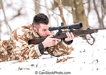 Hunter with a sniper rifle shooting during winter open season