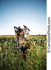 Hunter with bow walking through tall grass - Hunter with bow...