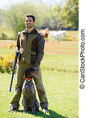 hunter with brown breed dog in the field