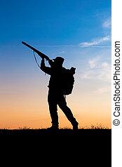 Hunter with shotgun in sunset