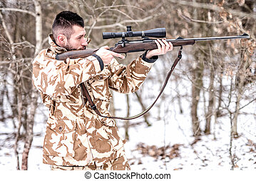 Hunter with sniper aiming and shooting in the forest during winter hunting season