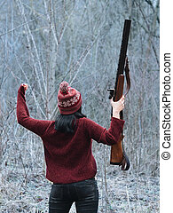 Hunter woman in burgundy warm clothes with gun. Girl hunting in the forest and rejoices her victory by raising rifle up after firing.