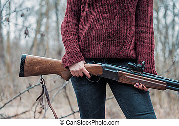 Hunter woman in burgundy warm clothes with gun. Girl hunting in the forest holding her rifle close up.