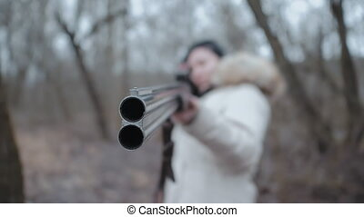 Hunter woman wearing warm coat targets the enemy on the battlefield with rifle. Unrecognizable girl training with a shotgun weapon in autumn forest. Slow motion. Focus on barrel