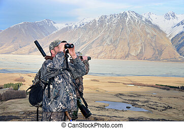 Hunters on the lookout - two hunters searching for Himalayan...