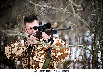 Hunting, army, military concept - sniper holding rifle and aiming at target in the forest during operation