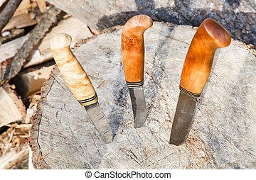 hunting knives thrust in tree stump - three hunting knives...