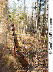 A hunting rifle leaning against a tree.