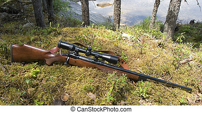 hunting rifle and riflescope in a forest near water