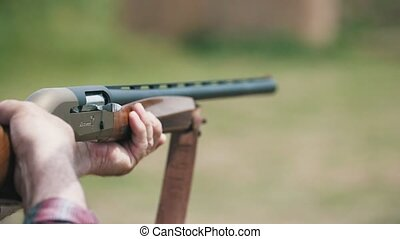 Exciting view of modern one-barrel rifle aiming and shooting at a clay pigeon. A white cartridge case tumbling out in slo-mo