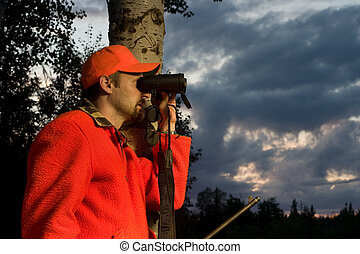 hunting season - hunter in high visibility clothing looking...