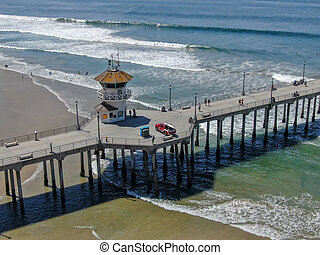 Huntington Pier with lifeguard tower for surfer. Southeast of Los Angeles. California, USA.