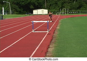 Hurdle - Woman runs and jumps a hurdle on the college track.