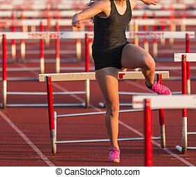 Hurdler tripping during a race on a track