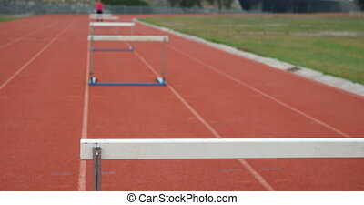Hurdles arranged on a running track at sports venue. Female athlete standing in the background 4k