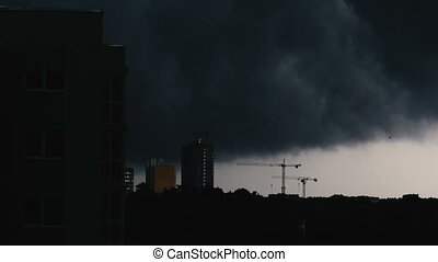 Hurricane. Black sky fills the city, it rains